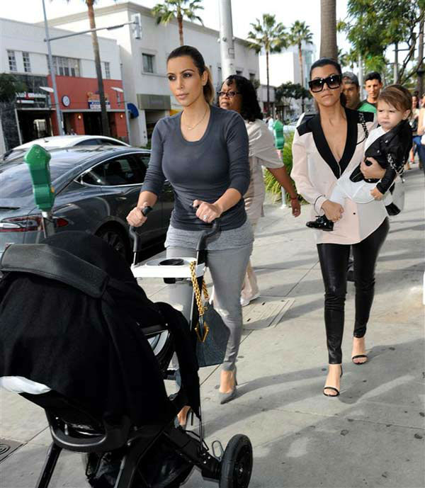 Kim Kardashian pushes North West in a stroller while out with Kourtney Kardashian and Kourtney's daughter Penelope Disick in Beverly Hills, California, on Dec. 16, 2013.