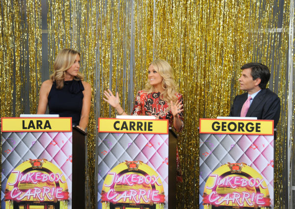 L-R: Guest co-host Carrie Underwood appears in between presenters Lara Spencer and George Stephanopoulos during a game show segment titled &#39;Jukebox Carrie&#39; on ABC&#39;s &#39;Good Morning America&#39; &#40;&#39;GMA&#39;&#41; on Aug. 12, 2013.  <span class=meta>(ABC Photo&#47; Donna Svennevik)</span>