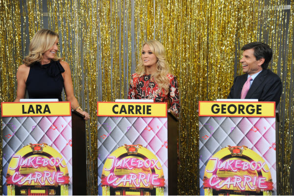 "<div class=""meta ""><span class=""caption-text "">L-R: Guest co-host Carrie Underwood appears in between presenters Lara Spencer and George Stephanopoulos during a game show segment titled 'Jukebox Carrie' on ABC's 'Good Morning America' ('GMA') on Aug. 12, 2013.  (ABC Photo / Donna Svennevik)</span></div>"