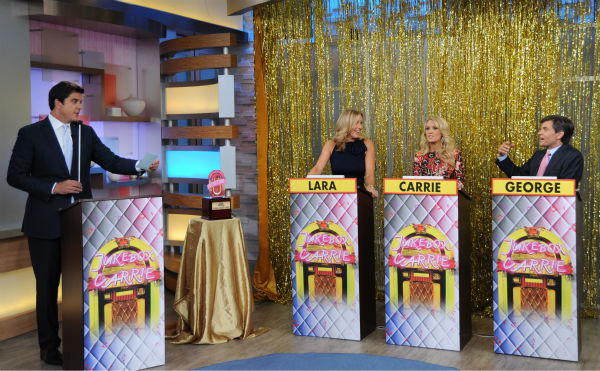 L-R: Guest co-host Carrie Underwood appears in between presenters Lara Spencer and George Stephanopoulos during a game show segment