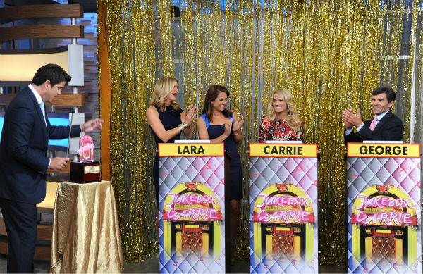 "<div class=""meta image-caption""><div class=""origin-logo origin-image ""><span></span></div><span class=""caption-text"">L-R: Guest co-host Carrie Underwood appears in between presenters Lara Spencer and George Stephanopoulos during a game show segment titled 'Jukebox Carrie' on ABC's 'Good Morning America' ('GMA') on Aug. 12, 2013. Pictured left: Josh Elliot. (ABC Photo / Donna Svennevik)</span></div>"