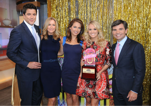 L-R: Presenters Josh Elliot, Lara Spencer and Ginger Zee, guest co-host Carrie Underwood -- holding her &#39;Jukebox Carrie&#39; trophy -- and presenter George Stephanopoulos appear on ABC&#39;s &#39;Good Morning America&#39; &#40;&#39;GMA&#39;&#41; on Aug. 12, 2013. <span class=meta>(ABC Photo &#47; Donna Svennevik)</span>