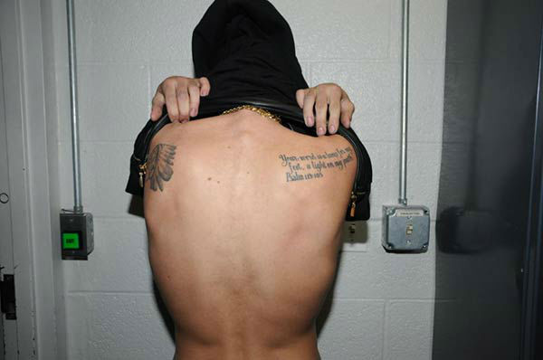 Justin Bieber appears at the Miami Beach Police Department following his January 2014 arrest. He was asked to show his identifying marks on his body while being processed in jail. <span class=meta>(Miami Beach Police Department)</span>