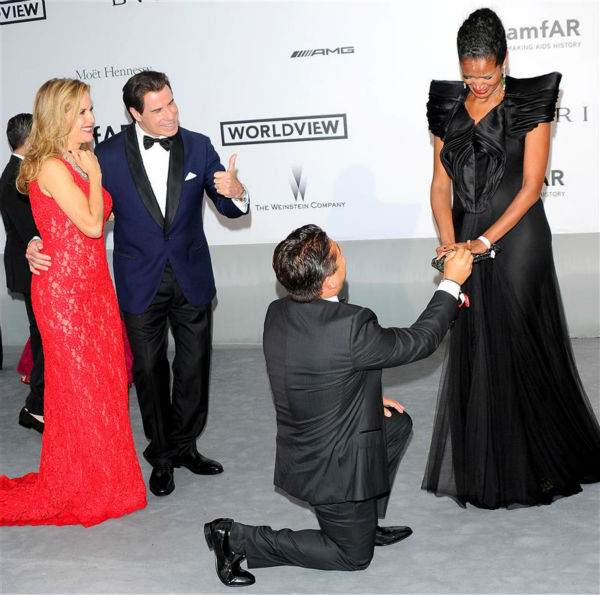 John Travolta and wife Kelly Preston watch Oscar Generale, producer of the family&#39;s new animated film &#39;Gummy Bear The Movie,&#39; propose to his girlfriend, actress and model Denny Mendez, who got emotional and accepted, at the amfAR&#39;&#39;s 21st Cinema Against AIDS gala at the 67th Cannes Film Festival in France on May 22, 2014. <span class=meta>(Alberto Terenghi &#47; IPA &#47; Startraksphoto.com)</span>
