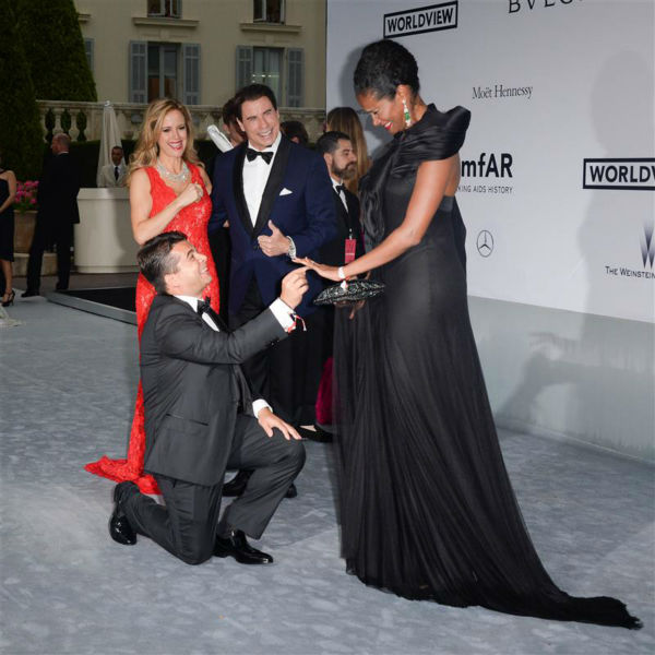 John Travolta and wife Kelly Preston watch Oscar Generale, producer of the family&#39;s new animated film &#39;Gummy Bear The Movie,&#39; propose to his girlfriend, actress and model Denny Mendez, who got emotional and accepted, at the amfAR&#39;s 21st Cinema Against AIDS gala at the 67th Cannes Film Festival in France on May 22, 2014. <span class=meta>(Lionel Hahn &#47; Abaca &#47; Startraksphoto.com)</span>