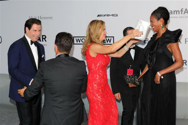 John Travolta and wife Kelly Preston congratulate Oscar Generale, producer of the family&#39;s new animated film &#39;Gummy Bear The Movie,&#39; and girlfriend, actress and model Denny Mendez, after he proposed to her at the amfAR&#39;s 21st Cinema Against AIDS gala at the 67th Cannes Film Festival in France on May 22, 2014. <span class=meta>(Alberto Terenghi &#47; IPA &#47; Startraksphoto.com)</span>