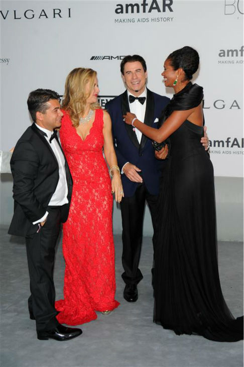 John Travolta and wife Kelly Preston appear with Oscar Generale, producer of the family&#39;s new animated film &#39;Gummy Bear The Movie,&#39; and girlfriend, actress and model Denny Mendez, after he proposed to her at the amfAR&#39;s 21st Cinema Against AIDS gala at the 67th Cannes Film Festival in France on May 22, 2014. <span class=meta>(Alberto Terenghi &#47; IPA &#47; Startraksphoto.com)</span>