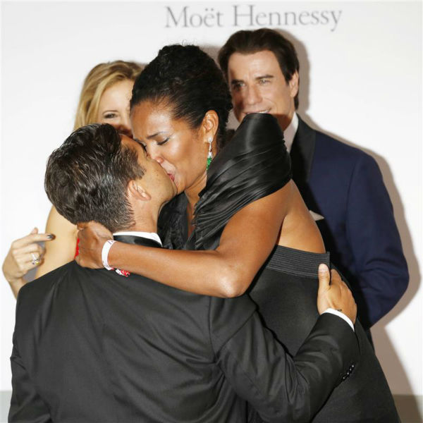 John Travolta and wife Kelly Preston watch Oscar Generale, producer of the family&#39;s new animated film &#39;Gummy Bear The Movie,&#39; propose to his girlfriend, actress and model Denny Mendez, who got emotional and accepted, at the amfAR&#39;s 21st Cinema Against AIDS gala at the 67th Cannes Film Festival in France on May 22, 2014. <span class=meta>(Future Image &#47; Startraksphoto.com)</span>
