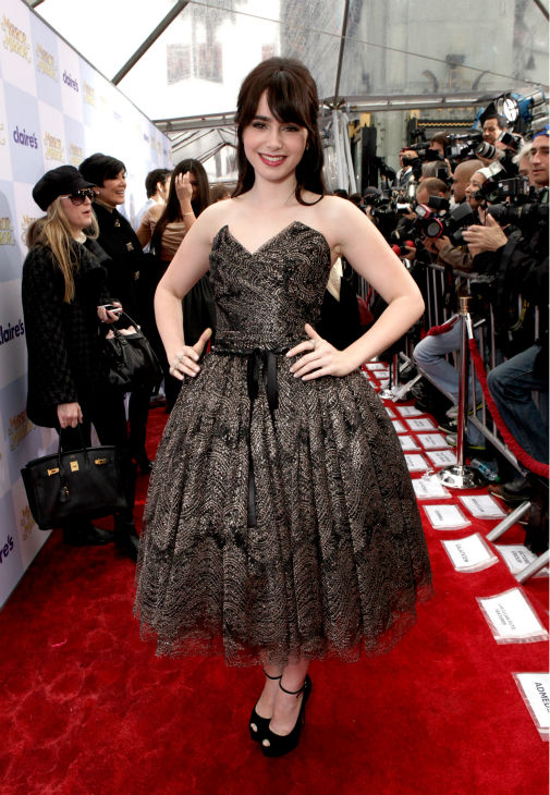 Lily Collins arrives at the premiere of &#39;Mirror Mirror&#39; at the Grauman&#39;s Chinese Theatre on March 17, 2012 in Hollywood, California. The actress, who plays Snow White, donned a strapless, black and gold Dolce and Gabbana tulle dress with a bell-shaped, tea-length skirt. <span class=meta>(Todd Williamson &#47; Getty Images For Relativity Media)</span>