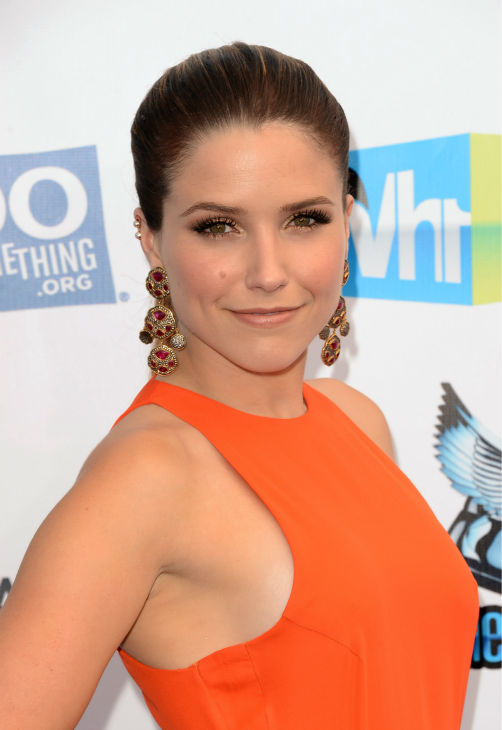 "<div class=""meta ""><span class=""caption-text "">Sophia Bush of 'One Tree Hill' arrives at the 2012 Do Something Awards at Barker Hangar on August 19, 2012 in Santa Monica, California. She is wearing an orange Olcay Gulsen Spring 2012 gown, a Sutra cocktail ring, Arunashi gold bangles and Sutra cuffs and is carring a Judith Leiber clutch. (Jason Merritt / Getty Images)</span></div>"