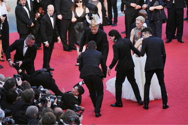 Security officials try to restrain notorious prankster of celebrities, Ukrainian reporter Vitalii Sediuk, after he crawled under actress America Ferrera&#39;s ball gown at a screening of &#39;How To Train Your Dragon 2&#39; at the 2014 Cannes Film Festival on Friday, May 16, 2014. Also pictured: Kit Harington and Cate Blanchett. <span class=meta>(Aurore Marechal &#47; ABACA &#47; Startraksphoto.com)</span>