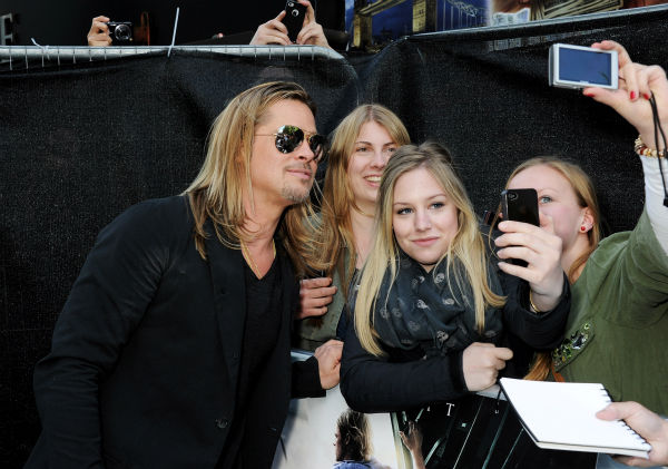 Cast member Brad Pitt poses for photos with fans at the world premiere of &#39;World War Z&#39; at the Empire Cinema Leicester Square in London on June 2, 2013. <span class=meta>(Dave M. Benett &#47; WireImage for Paramount)</span>