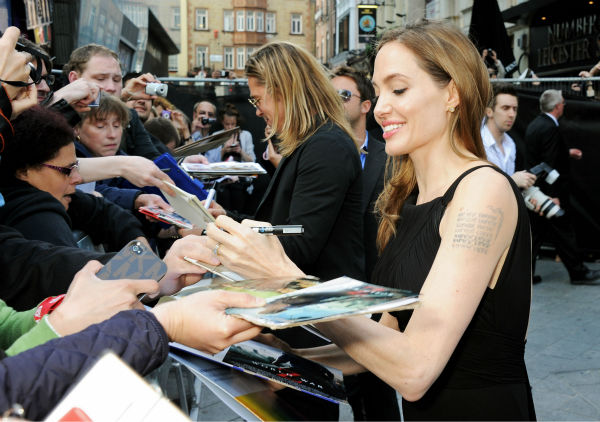 "<div class=""meta image-caption""><div class=""origin-logo origin-image ""><span></span></div><span class=""caption-text"">Angelina Jolie signs autographs for fans at the world premiere of 'World War Z,' which stars fiance Brad Pitt, at the Empire Cinema Leicester Square in London on June 2, 2013. (Dave M. Benett / WireImage for Paramount)</span></div>"