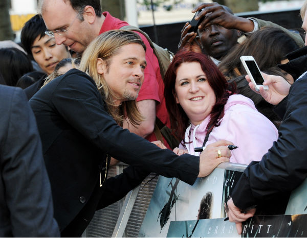 "<div class=""meta image-caption""><div class=""origin-logo origin-image ""><span></span></div><span class=""caption-text"">Cast member Brad Pitt poses for photos with fans at the world premiere of 'World War Z' at the Empire Cinema Leicester Square in London on June 2, 2013. (Dave M. Benett / WireImage for Paramount)</span></div>"