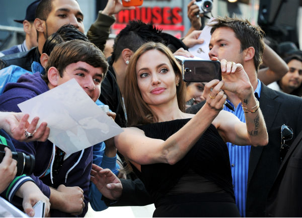 "<div class=""meta image-caption""><div class=""origin-logo origin-image ""><span></span></div><span class=""caption-text"">Angelina Jolie poses for photos with fans at the world premiere of 'World War Z,' which stars fiance Brad Pitt, at the Empire Cinema Leicester Square in London on June 2, 2013. (Dave M. Benett / WireImage for Paramount)</span></div>"