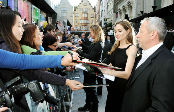 "<div class=""meta ""><span class=""caption-text "">Angelina Jolie signs autographs for fans at the world premiere of 'World War Z,' which stars fiance Brad Pitt, at the Empire Cinema Leicester Square in London on June 2, 2013. (Dave M. Benett / WireImage for Paramount)</span></div>"