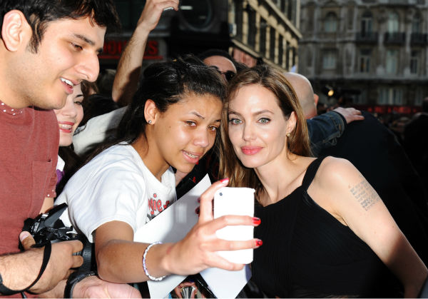 Angelina Jolie poses for a photo with a fan at the world premiere of &#39;World War Z,&#39; which stars fiance Brad Pitt, at the Empire Cinema Leicester Square in London on June 2, 2013. <span class=meta>(Stuart C. Wilson &#47; Getty Images for Paramount Pictures International)</span>