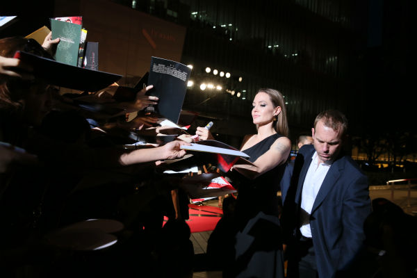 Angelina Jolie signs autographs at the &#39;World War Z&#39; premiere at Roppongi Hills in Tokyo, Japan on July 29, 2013. She is wearing a black, one-shoulder Saint Laurent gown. <span class=meta>(Ken Ishii &#47; Getty Images for Paramount Pictures)</span>