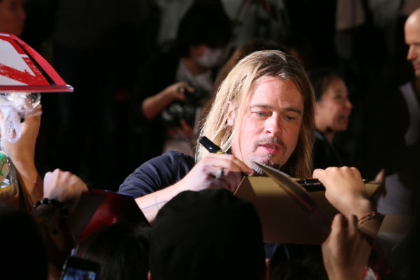 "<div class=""meta image-caption""><div class=""origin-logo origin-image ""><span></span></div><span class=""caption-text"">Brad Pitt signs autographs at the 'World War Z' premiere at Roppongi Hills in Tokyo, Japan on July 29, 2013. (Ken Ishii / Getty Images for Paramount Pictures)</span></div>"