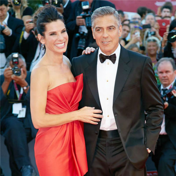 "<div class=""meta image-caption""><div class=""origin-logo origin-image ""><span></span></div><span class=""caption-text"">Sandra Bullock and George Clooney walk the red carpet at the premiere of the film 'Gravity' at the 70th annual Venice International Film Festival on Aug. 28, 2013. She is wearing a red, silk, strapless J. Mendel Resort 2014 'Siren' gown. (Action Press / Startraksphoto.com)</span></div>"