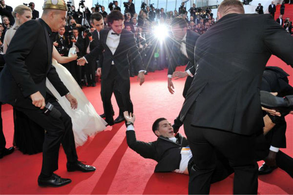 A security official tries to restrain notorious prankster of celebrities, Ukrainian reporter Vitalii Sediuk, after he crawled under actress America Ferrera&#39;s ball gown at a screening of &#39;How To Train Your Dragon 2&#39; at the 2014 Cannes Film Festival on Friday, May 16, 2014. Also pictured: Kit Harington. <span class=meta>(Camilla Morandi &#47; IPA &#47; startraksphoto.com)</span>
