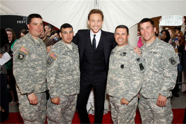 Tom Hiddleston poses with U.S. military men at the premiere of Marvel's 'The Avengers' at the Tribeca Film Festival in New York on April 28, 2012.