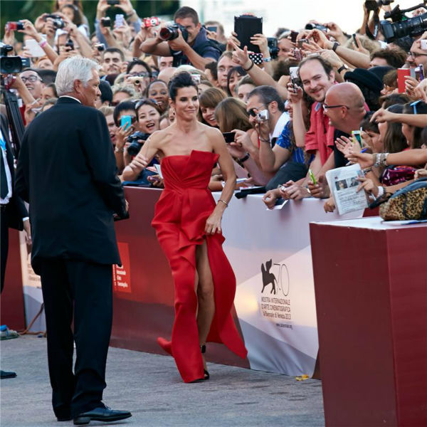 Sandra Bullock walks the red carpet and greets fans at the premiere of the film &#39;Gravity&#39; at the 70th annual Venice International Film Festival on Aug. 28, 2013. She is wearing a red, silk, strapless J. Mendel Resort 2014 &#39;Siren&#39; gown. <span class=meta>(Action Press &#47; Startraksphoto.com)</span>