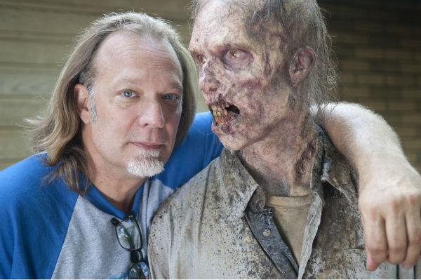 "<div class=""meta ""><span class=""caption-text "">Co-Executive Producer/SFX Makeup Supervisor Greg Nicotero and an actor dressed as a Walkers appear on the set of AMC's 'The Walking Dead's season 4 midseason premiere, titled 'After,' which aired on Feb. 9, 2014. (Gene Page / AMC)</span></div>"