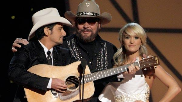 Host Brad Paisley, left, Hank Williams Jr., center, and hostess Carrie Underwood speak during the 45th Annual CMA Awards in Nashville, Tenn., on Wednesday, Nov. 9, 2011. - Provided courtesy of AP / Mark Humphrey