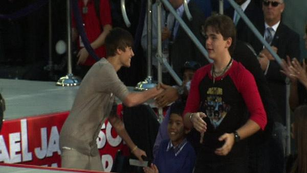 Justin Bieber (left) shakes the hand of an unidentified audience member as Blanket and Prince Jackson (right) look on at Michael Jackson's hand and footprint ceremony at the Grauman's Chinese Theatre on Jan. 26, 2012.