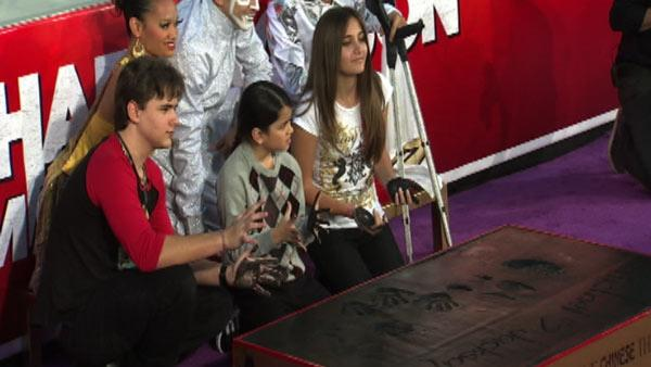 Michael Jackson's children Prince (left), Blanket (middle) and Paris place their hands in cement along an imprint of thei