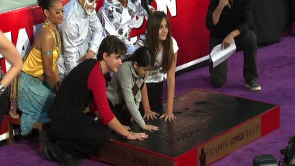 Michael Jacksons children Prince (left), Blanket (middle) and Paris place their hands in cement along an imprint of their fathers sequined globe and dance shoes at a ceremony at the Graumans Chinese Theatre on Jan. 26, 2012. - Provided courtesy of OTRC
