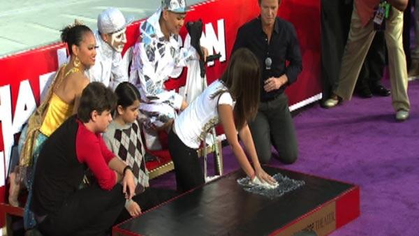 Paris Jackson places her late father Michael Jackson's sequined glove on plastic on top of cement and pushes down to create a han