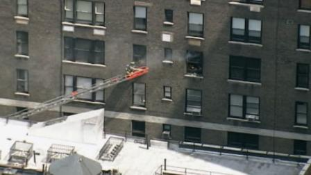 A firefighter climbs onto a ladder placed outside a New York apartment building where Robert De Niro lives, on June 8, 2012.