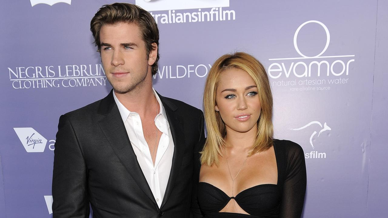 Liam Hemsworth, left, an honoree at the Australians in Film 8th Annual Breakthrough Awards, poses with his fiance Miley Cyrus on the red carpet in Los Angeles on Wednesday, June 27, 2012.