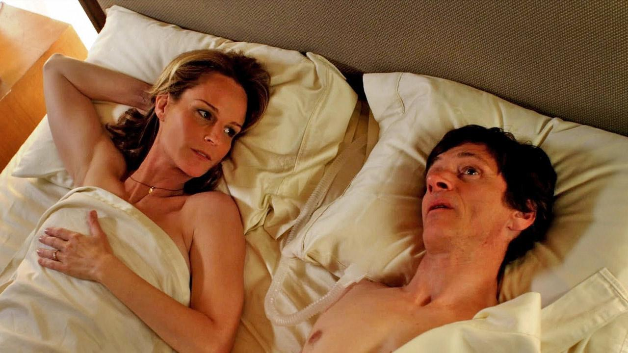 Helen Hunt and John Hawkes appear in a scene from the film The Surrogate. Hawkes plays a poet and journalist in an iron lung who contacts a professional sex surrogate, portrayed by Hunt, to help him after he decides he no longer wishes to be a virgin.