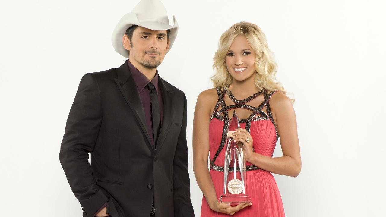 Brad Paisley and Carrie Underwood, wearing a Catherine Deane dress, appear in a publicity photo for the 2012 CMA Awards.