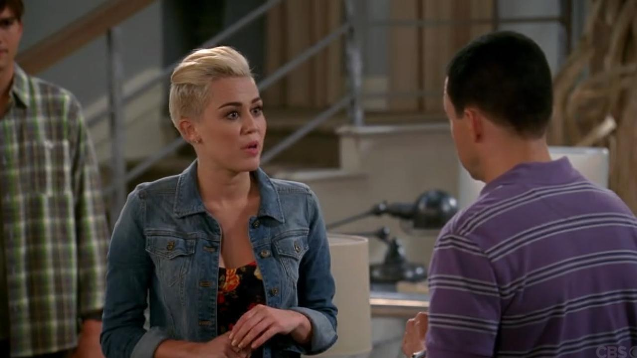 Ashton Kutcher, Miley Cyrus and Jon Cryer appear in a still from Two and a Half Men.