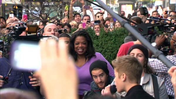 Oprah Winfrey watches on while Justin Bieber delivers a sidewalk performance for 'Oprah's Next Chapter' outside RL Restaurant in Chicag