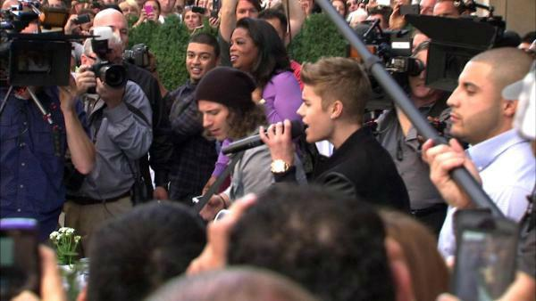 Oprah Winfrey watches on while Justin Bieber delivers a sidewalk performance for 'Oprah's Next Chapter' outside RL Restaurant in Chicago, Illinois on Wednesday, Oct. 24, 2012.