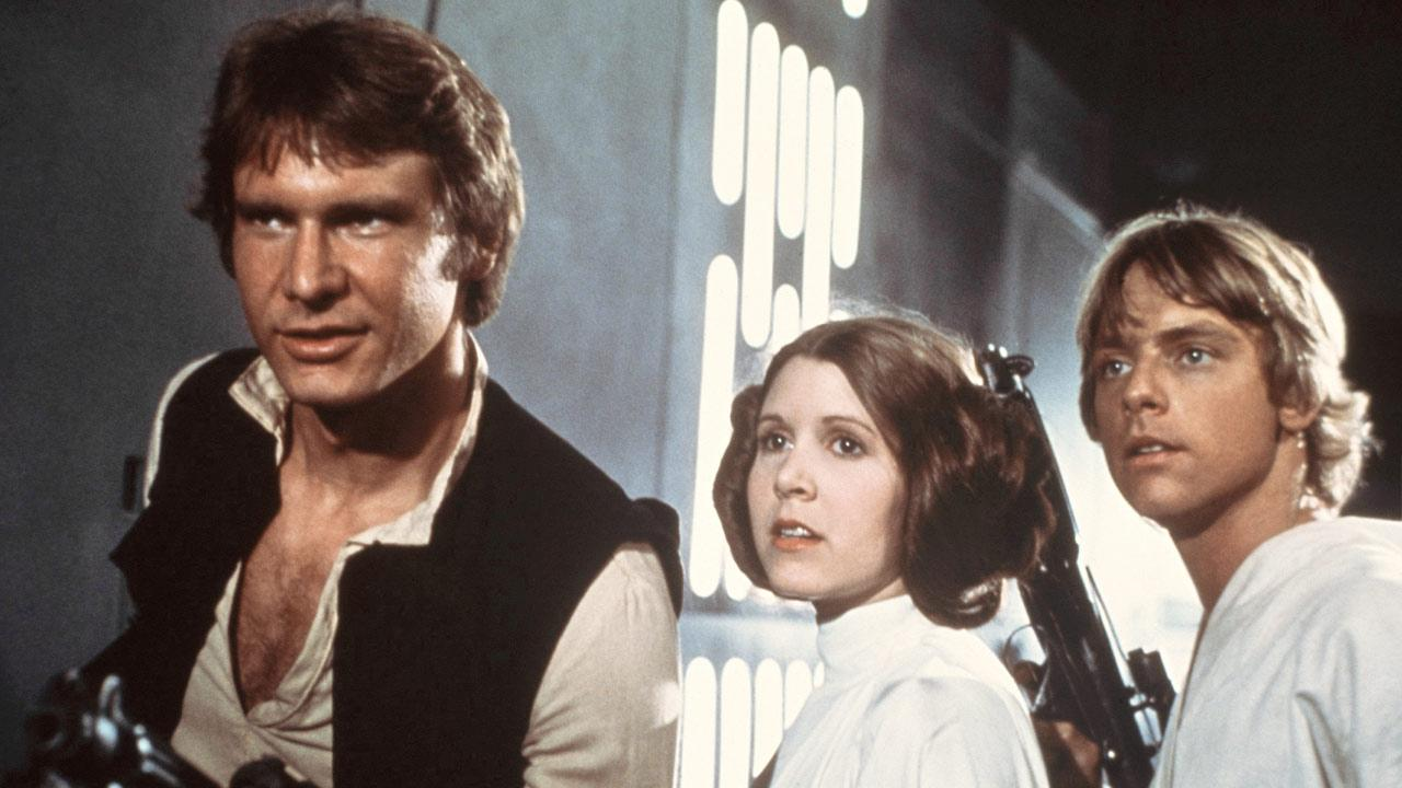 In this image provided by 20th Century-Fox Film Corporation, a scene from Star Wars movie released by 20th Century-Fox in 1977. From left are: Harrison Ford, Carrie Fisher, and Mark Hamill.