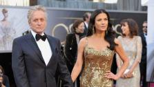 Catherine Zeta-Jones and Michael Douglas walk the red carpet at the 2013 Oscars on Sunday, February 24.