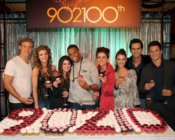 Pictured L-R: Trevor Donovan, AnnaLynne McCord, Shenae Grimes, Tristan Wilds, Jessica Stroup, Jessica Lowndes, Michael Steger and Matt Lanter celebrate the 100th episode of 90210 with cupcakes on Nov. 30, 2012. - Provided courtesy of Scott Alan Humbert / The CW Network