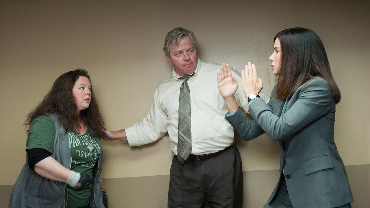 Sandra Bullock, Thomas F. Wilson and Melissa McCarthy appear in a scene from the 2013 movie The Heat. Bullock plays an FBI agent and McCarthy plays a foul-mouthed Boston cop. They team up to try to nab a ruthless drug lord.Twentieth Century Fox Film Corporation