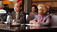 Dr. Joyce Brothers guest stars as Senator Diedre Kerner, (with guest star Clyde Kusatsu) who is on the Senate approval committee for the new JAG, on a 2004 episode of the CBS show JAG. - Provided courtesy of OTRC / Gale Adler / CBS / Paramount Television