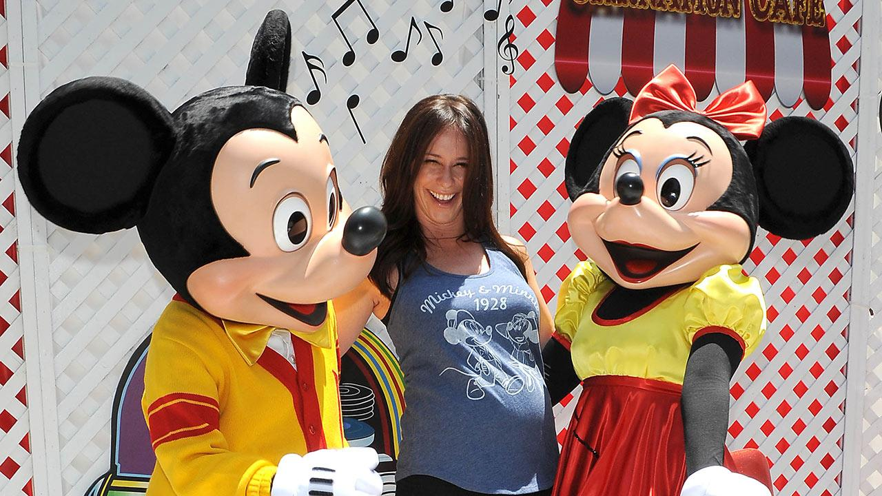 A pregnant Jennifer Love Hewitt poses with Mickey and Minnie Mouse at Old Navys Mickey Through The Decades Collection Launch at the Walt Disney Company studio lot in Burbank, California.