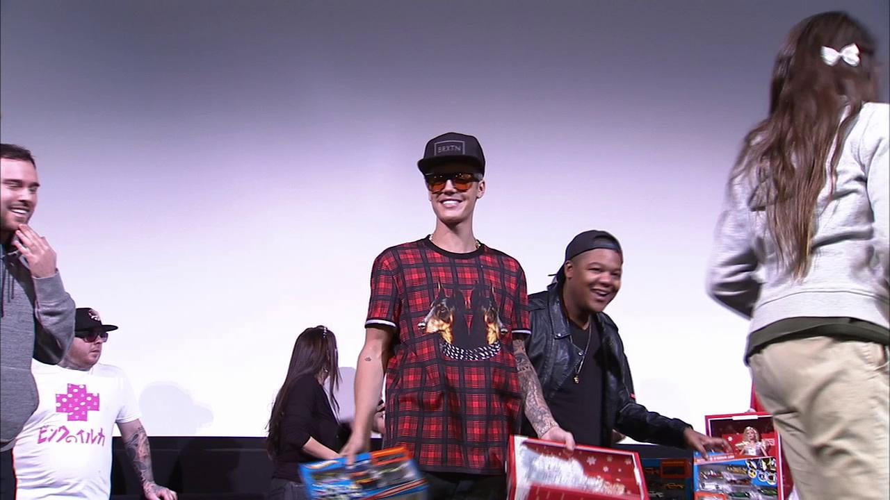 Justin Bieber surprises fans at a screening of his new movie Believe on Dec. 16, 2013. He handed out toys to a lucky group of Beliebers.