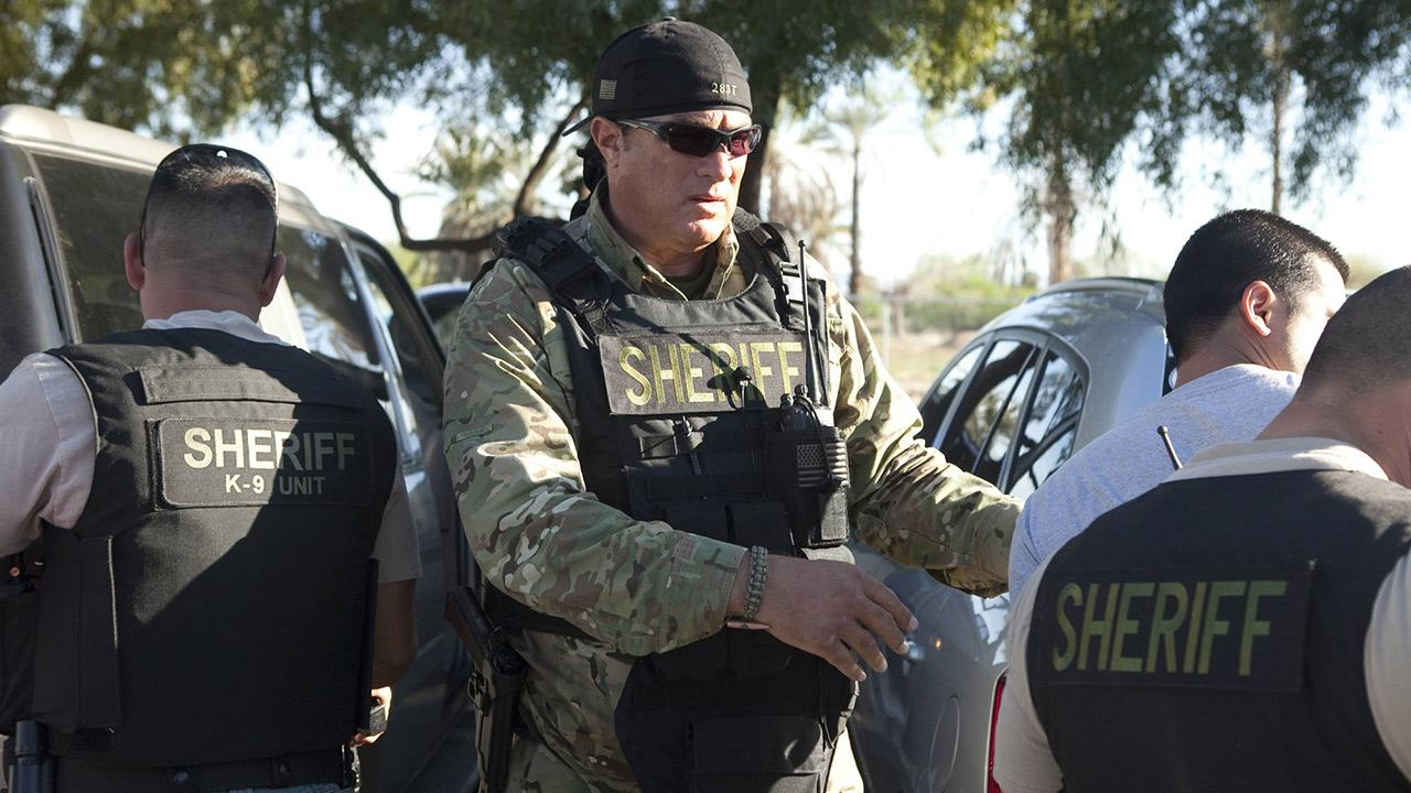 Steven Seagal appears in a 2014 promotional photo for his reality show: Steven Seagal - Lawman: Maricopa County, which airs on ReelzChannel.