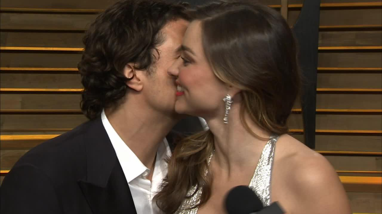 Orlando Bloom kisses estranged wife Mirana Kerr during her interview with OTRC.com at the Vanity Fair Oscars after party on March 2, 2014.