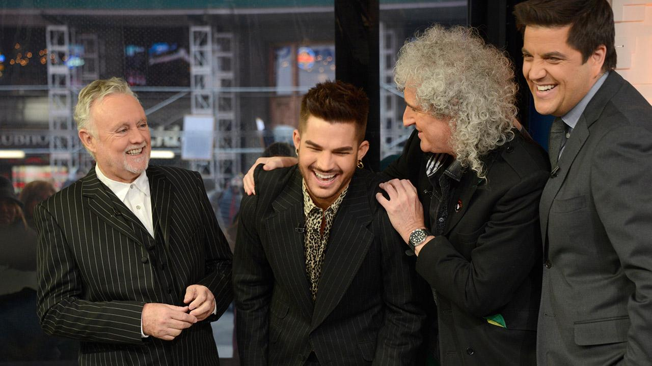 Adam Lambert appears with Queen members Brian May and Roger Taylor on ABCs Good Morning America as co-anchor Josh Elliot looks on. The American Idol alum announced he is touring with the legendary rock group.